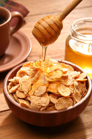 Breakfast scene. Honey pouring into a cereal bowl photo