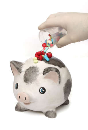 Pouring medicine pills over an infected piggy bank Stock Photo - 4836035