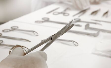 Doctor with surgical scissors at the operation room photo
