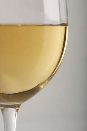 white wine glass: Close-up of a white wine glass over gray background