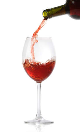 Pouring red wine into a glass isolated on white photo
