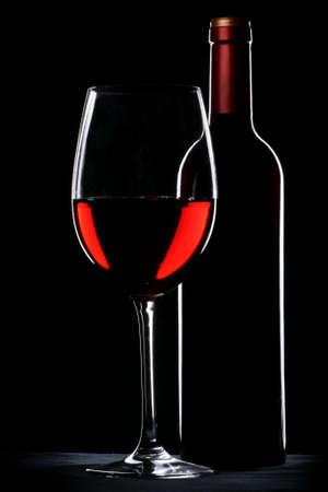 Rote Wein Flasche und Glas Silhouette über schwarzem Hintergrund Standard-Bild