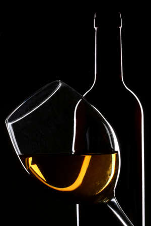 white wine bottle: White wine bottle and glass silhouette over black background Stock Photo