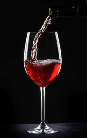 Pouring red wine into a glass over black background