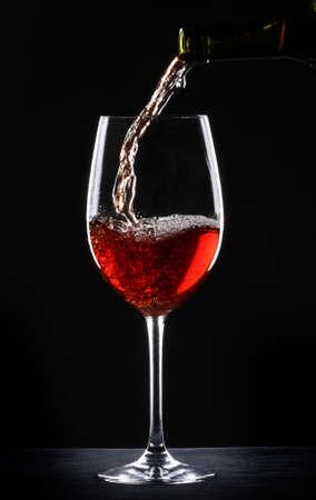 Pouring Rotwein in ein Glas über schwarzem Hintergrund Standard-Bild