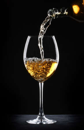 white wine bottle: Pouring white wine into a glass over black background Stock Photo