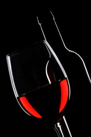 red taste: Red wine bottle and glass silhouette over black background Stock Photo