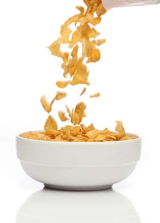 cereal: Verter copos de ma�z en un taz�n, sobre fondo blanco Foto de archivo