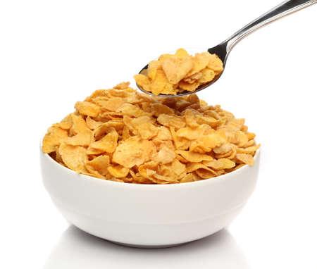 cereals: Copos de ma�z en una cuchara en un taz�n de fuente Foto de archivo