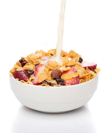 bowl of cereal: Pouring milk into a bowl of cornflakes and fruits Stock Photo