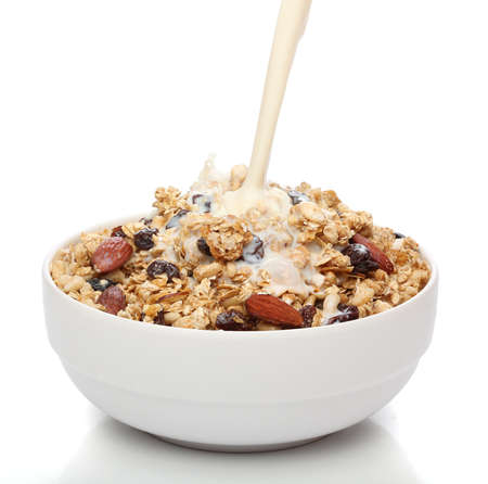 breakfast cereal: Pouring milk into a bowl with granola cereal