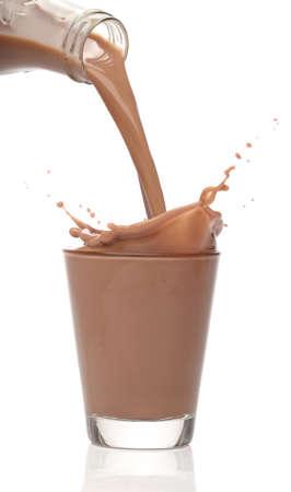 Flasche gießt Milch in ein Glas Schokolade