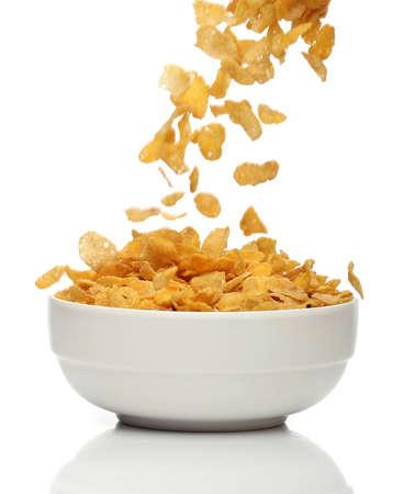 Gießen Cornflakes in eine Schüssel geben, über weißem Hintergrund