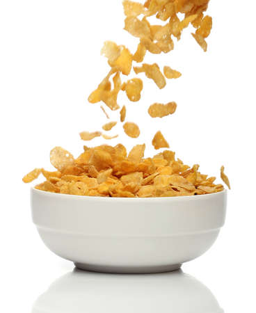 Pouring cornflakes into a bowl, over white background Stock Photo