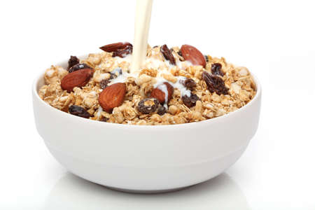 bowl of cereal: Pouring milk into a bowl with granola cereal