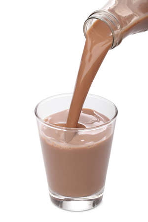 Bottle pouring milk chocolate into a glass Stock Photo