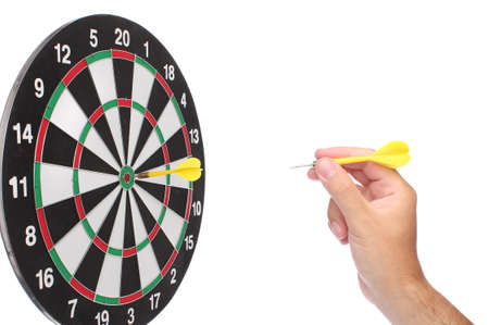 Hand throwing a yellow dart over white photo