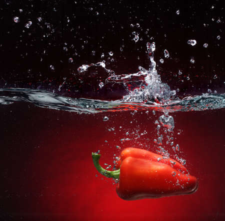falling water: Red pepper falling into water  Background in the same tone