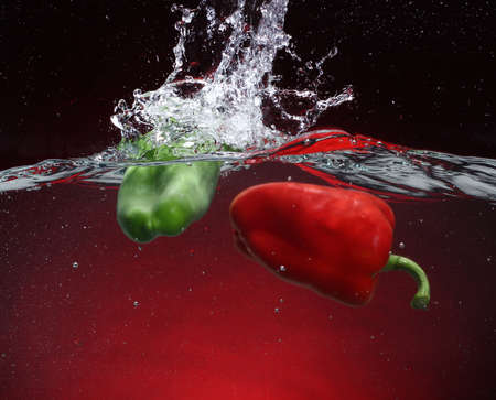 Two peppers falling into water  Red background