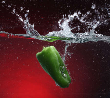 cheff: Green pepper falling into water  Red background
