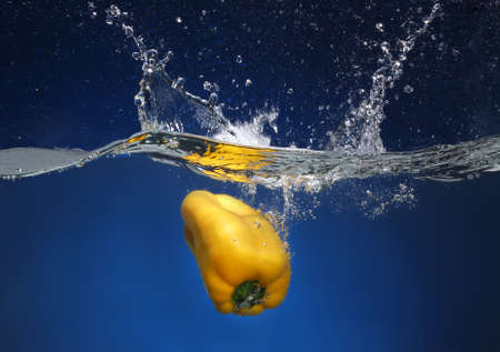 cheff: Yellow pepper falling into water  Blue background