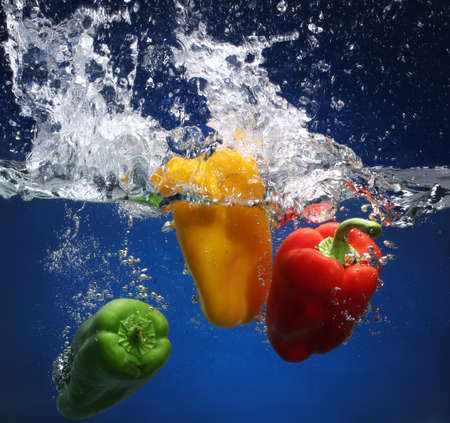 Three peppers falling into water  Blue background Stock Photo - 13978203