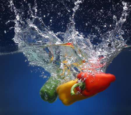 cheff: Three peppers falling into water  Blue background