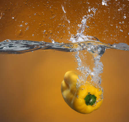 cheff: Yellow pepper falling into water  Background in the same tone