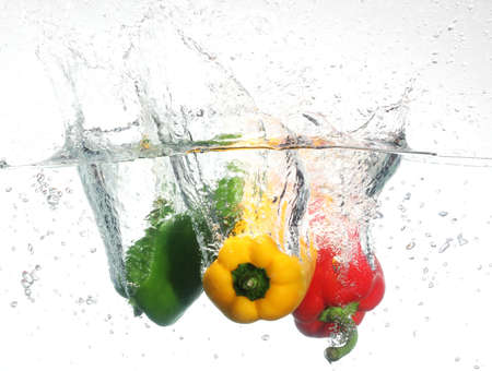 Drei Paprika fallen ins Wasser, auf weißem Hintergrund