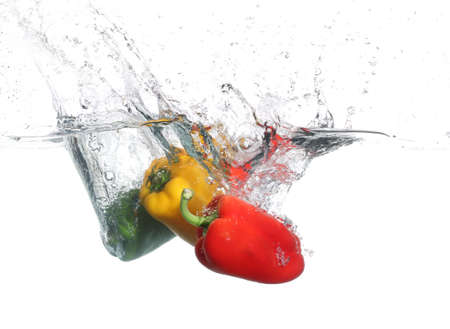 cheff: Three peppers falling into water, over white background Stock Photo