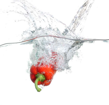 Red pepper falling into water over white background photo