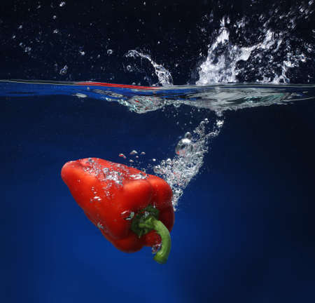 cheff: Red pepper falling into water  Blue background