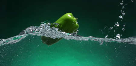 cheff: Green pepper falling into water  Green background