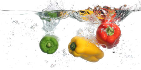 falling water: Three peppers falling into water, over white background Stock Photo