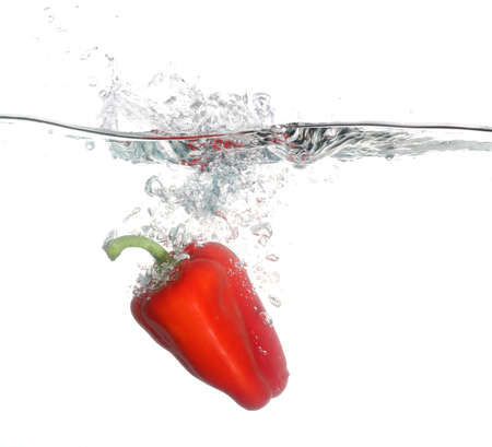 cheff: Red pepper falling into water over white background
