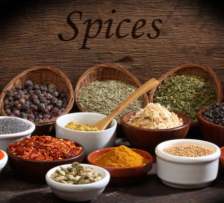 Various bowls of spices over wooden background  Colours and textures  photo