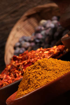 dryed: Three bowls of spices over wooden background  Cinnamon, chili, juniper Stock Photo
