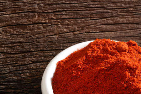 cheff: Bowl with paprika over a wooden background