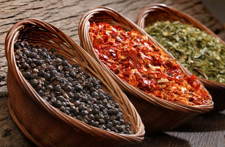 cheff: Three bowls with spices over wooden background  Ground chili, black pepper, parsley