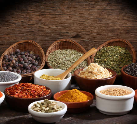 Different bowls of spices over a wooden background photo