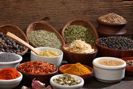 dryed: Different bowls of spices over a wooden background