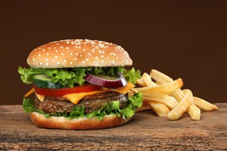 Tasty hamburger and french frites on wood background