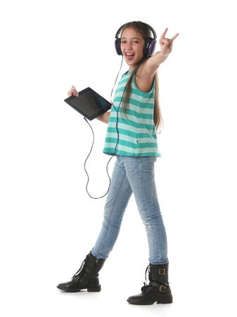 Beautiful preteen girl dancing and going crazy using a tablet computer and headphones