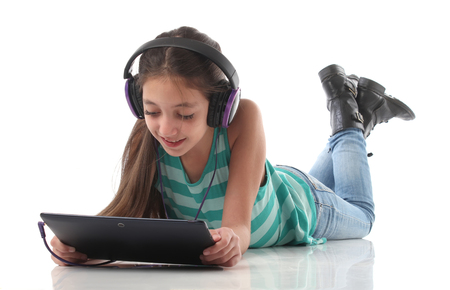 Beautiful preteen girl on the floor usin a tablet computer and headphones white background