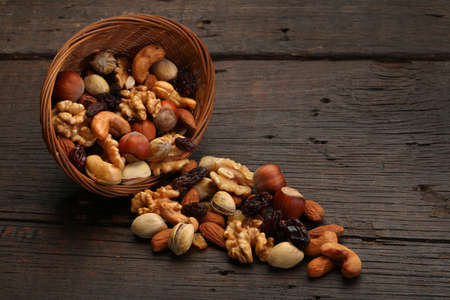 Mix of delicious nuts in a bowl, over a wooden background