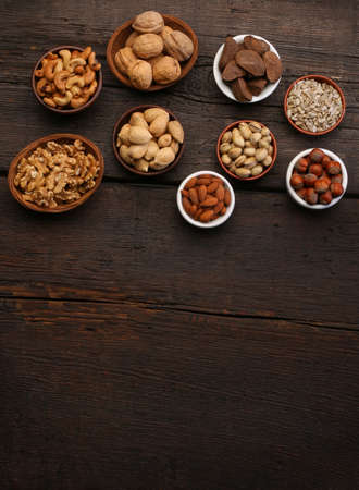 Group of delicious dried fruits over a wooden background. Nuts, almonds, pistachios Foto de archivo