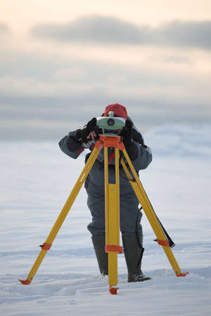 Surveyor at work with a leveling instrument Stock Photo