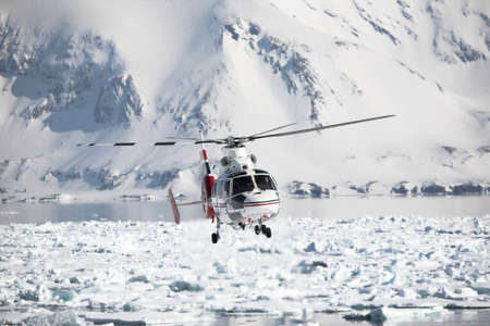 Helicopter during rescue operation over the frozen fjord in Arctic, Spitsbergen photo
