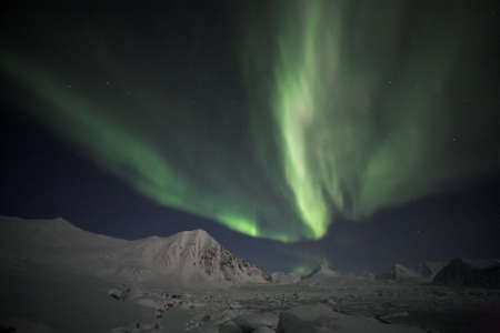 polar station: Enchanted Northern Lights over the Archipelago of Svalbard Stock Photo