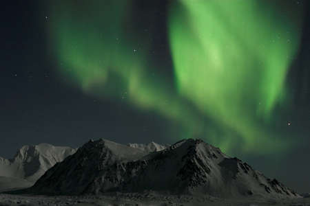 polar station: Northern lights over the mountains - Polar Night in the Arctic Stock Photo